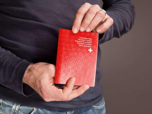 Ein-Mann-mit-einem-Schweizer-Reisepass-Symbolbild-